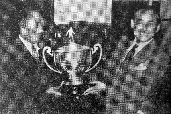 Carlos Cárdenas, presidente de Mariscal Sucre, sostiene junto a su vicepresidente el trofeo que se puso en disputa y que acabó ganando Universitario (Recorte: diario La Crónica)