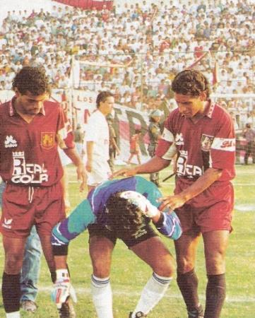 El golero Sergio Salazar es atendido por Giuliano Portilla y Raúl Mejía luego de ser agredido por la Trinchera Norte en el Lolo Fernández, en el Universitario - León del Descentralizado 1994 (Foto: revista Estadio)