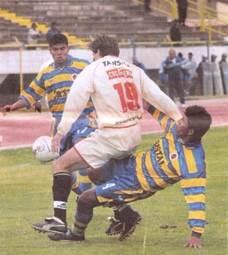 Martín Villalonga es encimado por Jorge Parihuana y Hansel Arriaga la tarde del lunes 30 de julio de 2001, cuando Unión Minas venció 1-0 a Universitario en el estadio Huancayo (Recorte: diario El Comercio, suplemento Deporte Total)