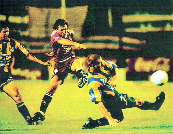 Gonzalo Belloso empalma un ajustado remate entre Daniel Kesman y Horacio Carbonari en la ida por la semifinal ante Rosario Central (Recorte: revista El Gráfico)