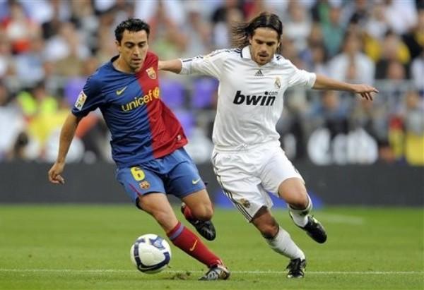 Fernando Gago extiende los brazos para marcar a Xavi (Foto: daylife.com)