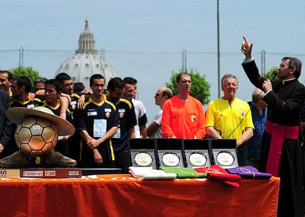 Siempre con El Vaticano como fondo, la imagen muestra una ceremonia de premiación con la Clerical Cup en primer plano (Foto: overheardinthesacristy.net)