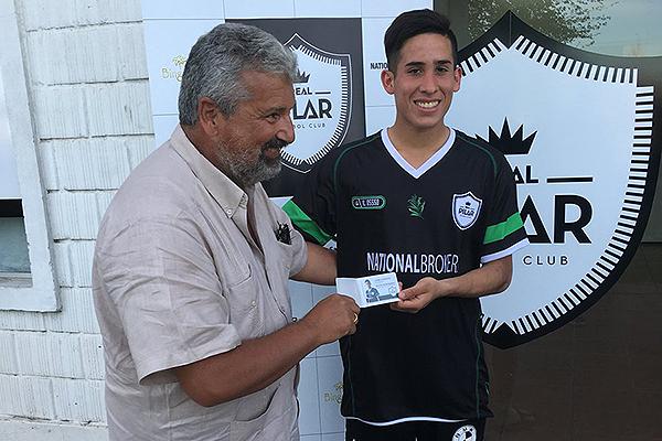 César Mansilla le otorga un premio a uno de los jugadores del Real Pilar. (Foto: Prensa AFA)
