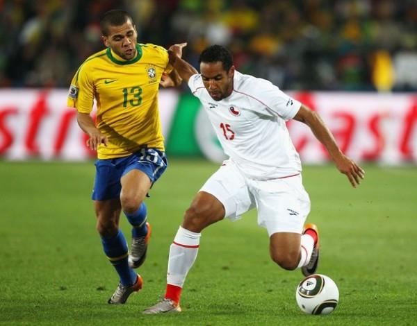 NO AVANZAS MAS. Parece decirle Dani Alves al chileno Beausejour. El brasileño avanza, Chile regresa a casa (Foto: AP)