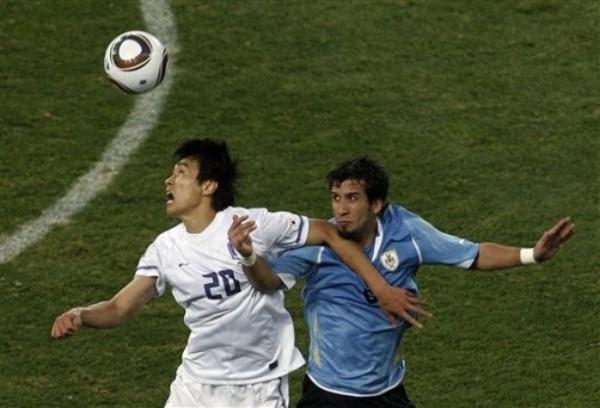 PIEZAS DE RECAMBIO. Mauricio Victorino disputa la posesión en el juego aéreo con Lee Dong-Gook. Ambos jugadores ingresaron en la etapa complementaria. (Foto: AP)