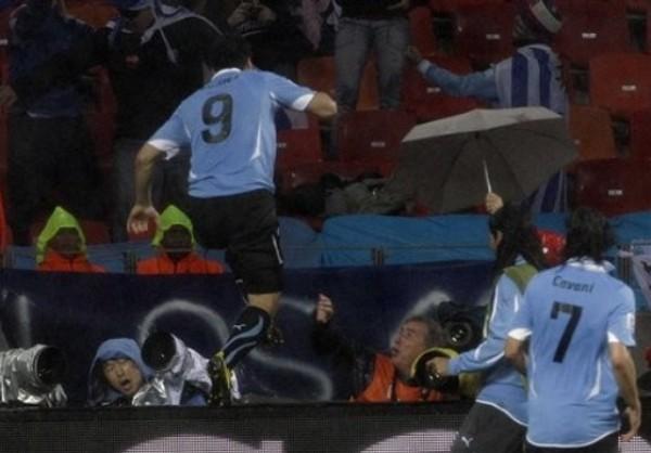 DERRIBANDO TODO. Luego de anotar el segundo tanto charrúa, Luis Suárez salta la publicidad estática y golpea a algunos fotógrafos que se encontraban detrás del arco surcoreano. (Foto: AP)