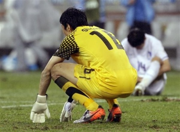 TRISTEZA ASIÁTICA. El guardavalla surcoreano, Jun Sung-Ryong permanece hincado sobre el terreno. Una dubitativa salida suya, propició el primer tanto del uruguayo Luis Suárez. (Foto: AP)