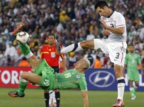 LA REDONDA ES MÍA. Hassan Yebda intenta con una chalaca ante la presencia de Bocanegra. Los argelinos no pudieron con el cerco norteamericano (Foto: AP)