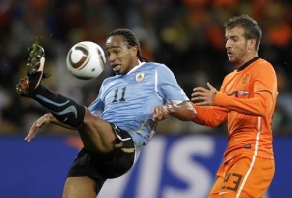 LO PINTA A RAFAEL. Álvaro Pereira se sacude de la marca de Rafael Van der Vaart (Foto: AP)