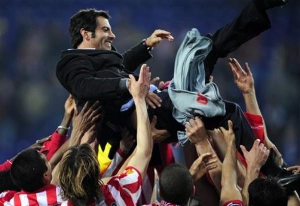 EL PADRE DE LA CRIATURA. Aun resistido por algunos sectores de la prensa española, Quique Sánchez Flores logró un éxito importantísimo en su carrera como técnico. Acá es lanzado por los aires por sus jugadores (Foto: AP)