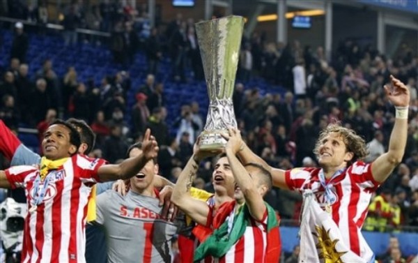 LA VUELTA TENÍAMOS QUE DAR. Forlán y el Atlético en pleno festejan con el trofeo de la Europa League en cancha del Hamburgo (Foto: AP)