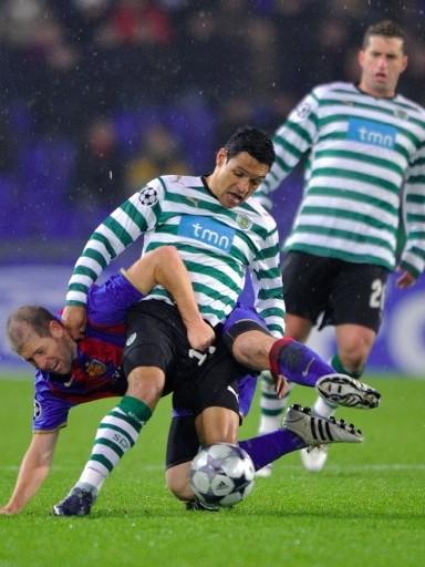 ENREDADOS. Derlei pelea en posición poco ortodoxa con el australiano Chipperfield del Basel. Sporting jugó tranquilo y ganó en Suiza (Foto: FIFA.com / AFP)