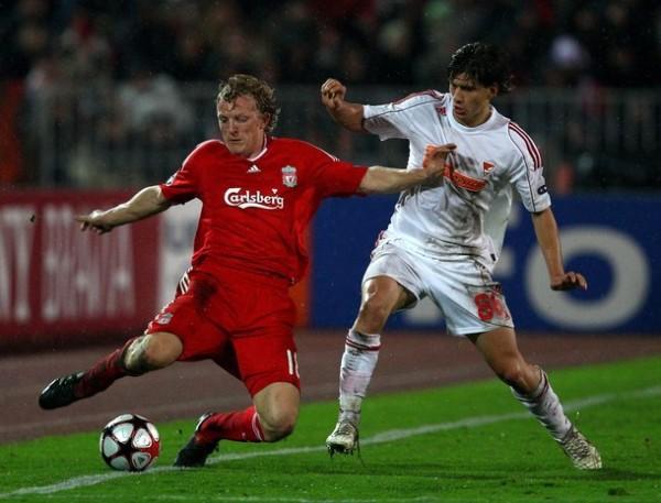 RED DE IMPOTENCIA. El holandés Dirk Kuyt no puede contener el balón ante el acecho de Zsolt Laczko. Liverpool ganó, pero no le alcanzó para clasificar (Foto: AP)