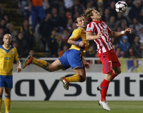 NO FUE UN CUENTO DE BRUJAS. Diego Forlán es estorbado por Paulo Gomes. Atlético Madrid por poco se complica ante el APOEL Nicosia. Con el empate, quedó en zona de la Europa League (Foto: AP)