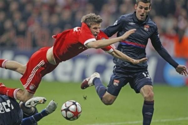VUELA VUELA. Thomas Müller sale despedido por los aires ante la marca de Cris. Bayern la pasó muy complicada por momentos en su estadio ante Lyon (Foto: AP)