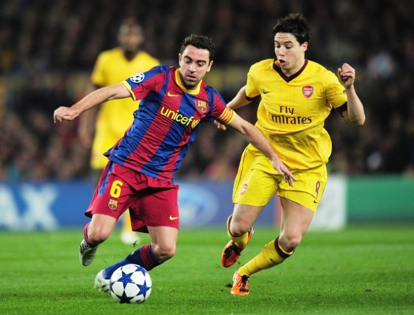 NO LO DEJEN PENSAR. Tal es la importancia de Xavi en Barcelona, que otro que es vital en el ataque de su equipo, Nasri, tuvo que sacrificarse para presionar el cerebro blaugrana. (Foto: AFP)