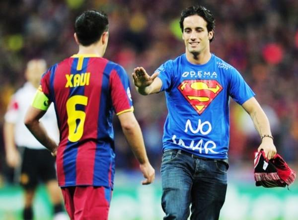 ¿Y TÚ? En medio de la etapa complementaria, un hincha con el polo de Superman se metió a la cancha para saludar a Xavi y Messi. (Foto: AFP)