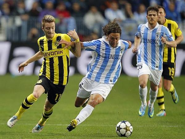 El choque de dos mediocampos fuertes como los del Málaga y el Dortmund se ve representado en esta disputa del balón entre Marco Reus y Manuel Iturra (Foto: AFP)