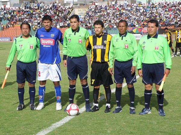 UNO POR BANDO. La terna arbitral del cotejo posa junto a los capitanes de ambos elencos: Freddy Tejada (FBC Aurora) y Luis Noriega (Unicachi). (Foto: Iván Carpio / DeChalaca.com)
