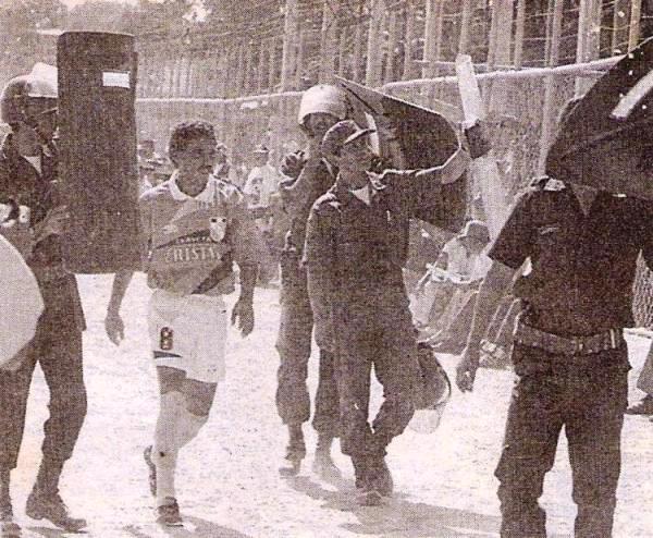El 'Chorri' se va resguardado por fuerzas policiales en Sullana luego de ser expulsado ante Alianza Atlético en el Descentralizado 1996. (Recorte: diario El Bocón)