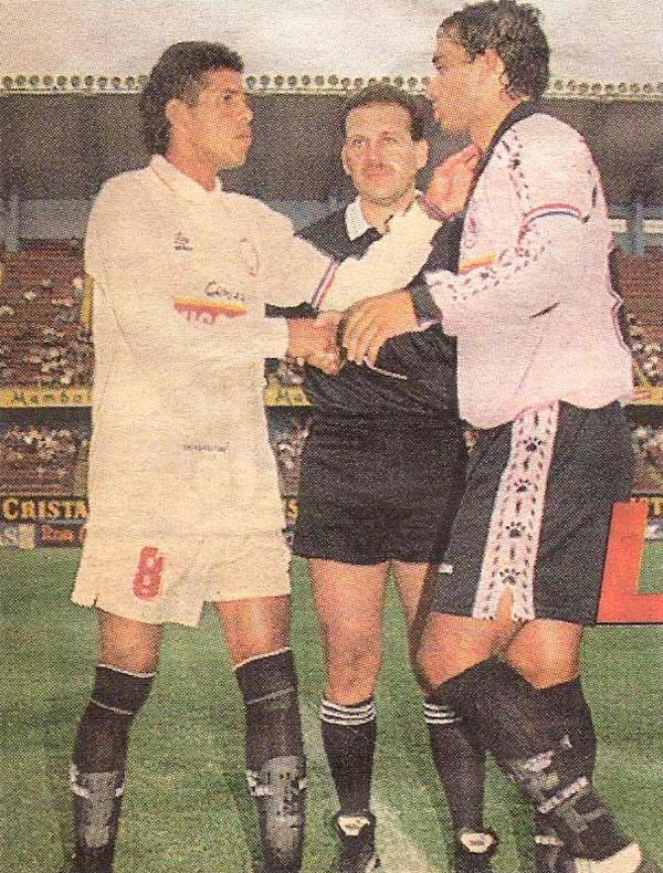 Los capitanes José Carranza y Roberto Martínez se saludan ante la mirada del árbitro Alberto Tejada. La presencia del ex jugador crema con casaquilla rosada había calentado la semana (Recorte: diario Líbero)
