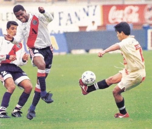 José Pereda remata ante el edil Alexis Prado la tarde en que anotó su último gol en el fútbol peruano antes de marcharse a Boca Juniors, en el Clausura 1998 (Recorte: revista Don Balón Perú)