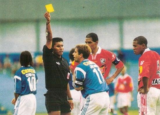 Iván Chang le muestra una tarjeta amarilla a Julinho la tarde en que Cristal derrotó 2-1 a Cienciano por el Apertura 2001. Aquella vez, el de negro tuvo una actuación nefasta (Recorte: revista El Gráfico Perú)