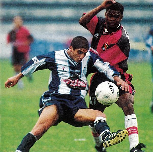 Guillermo Salas pugna por controlar la pelota ante el asedio del delantero colombiano Carlos Castillo (Recorte: revista El Gráfico Perú)