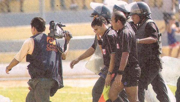 Ya se suscitó el acto bochornoso en la tribuna y el juez Martín Cabrera se retira del gramado por la agresión a su juez de línea. El partido había sido suspendido (Recorte: diario El Bocón)