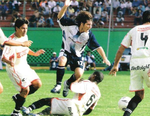 Sobre el antiguo césped natural del Nacional, José Mendoza barre a Gustavo Barros Schelotto. Fue por el Apertura 2005, en clásico que acabó igualado 2-2. (Recorte: revista El Gráfico Perú)