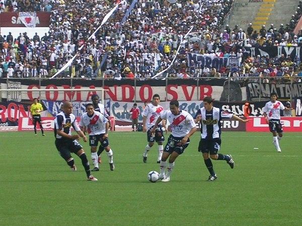 Y LA GENTE ESTÁ. Molina, que actuó esta vez como volante izquierdo en Gálvez, avanza ante la marca de González. Al fondo, la hinchada íntima, que llegó en buen número al Centenario Manuel Rivera Sánchez (Foto: Diario de Chimbote)