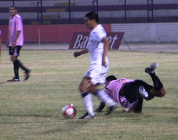 UNA NUEVA CAÍDA. Pérez va directo al piso luego de disputar un balón con Muente. Los rosados acumularon una nueva derrota y comienzan a comprometerse con el descenso (Foto: Wagner Quiroz / DeChalaca.com)