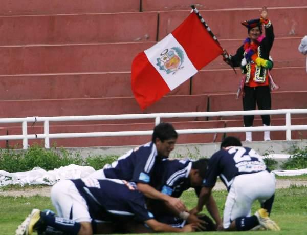 EL HINCHA I. Mientras los jugadores de Cienciano celebran un tanto, un peculiar hincha que porta una bandera peruana saluda a las cámaras que lo captan. (Foto: diario La Voz de Arequipa)
