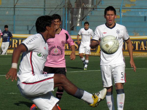 SAQUE SI QUIERE GANAR. Carlos Fernández toma el balón en su área, y ante la presión de Jeremías Caggiano, termina echando el esférico. (Foto: José Salcedo / DeChalaca.com)