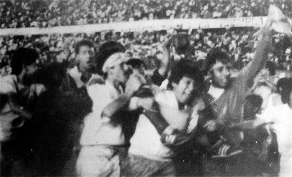 El desborde popular se hizo sentir en la vuelta olímpica de Cristal en 1991, como con un jugador celeste del que solo se llegan a apreciar las medias y los botines (Recorte: revista Estadio)