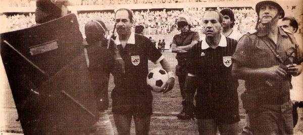 Así salió de la cancha 'Paquirri' Ramírez el día de su último partido con la insignia FIFA, rodeado de policías y con el balón en la mano. A su costado lo acompaña Sergio Leiblinger (Recorte: revista Estadio)