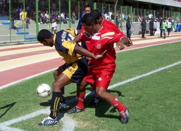 PROTEGE EL BALÓN. Luis Sánchez logra retener un balón a pesar de la marca de dos hombres de Acosvinchos. (Foto: Freddy Mamaní)