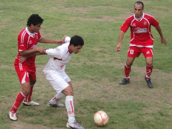 JUEGO DE MANOS. Sotomayor intenta mantener el control del balón pese a los forcejeos con un hombre de Acosvinchos. (Foto: Aldo Ramírez / DeChalaca.com)