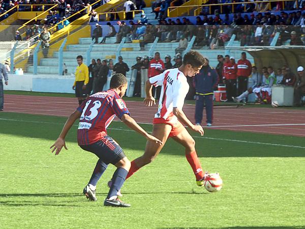 Miguel Curiel intenta sacarse la marca de Carlos Castillo en un duelo que resultó parejo a lo largo del encuentro en el Enrique Torres Belón (Foto: Puno Deportes)