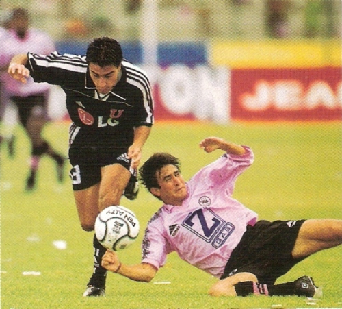 Rómulo 'Copete' Fernández rueda ante la marca de Roberto Cáceres durante la derrota 0-2 de Sport Boys a manos de la Universidad de Chile en el Callao por la Copa Libertadores 2001 (Recorte: revista El Gráfico Perú)