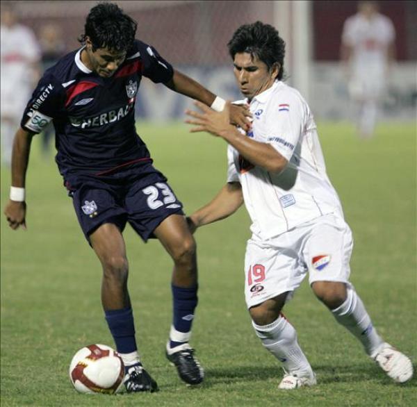 CLASIFICACIÓN PELEADA. Quinteros y Cáceres luchan la bola. San Martín la tiene más fácil que los paraguayos (Foto: EFE)