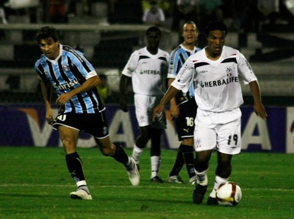 PASAR Y PASAR. Fernández conduce el balón ante la mirada del argentino Herrera, quien ingresó en el complemento en Gremio (Foto: Andrés Durand / DeChalaca.com)