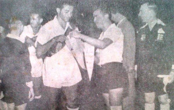 Guillermo Delgado y José Bustamante, capitanes, cambian banderines ante la mirada del juez inglés Rhoden antes del Perú - Bolivia. (Recorte: diario La Crónica)