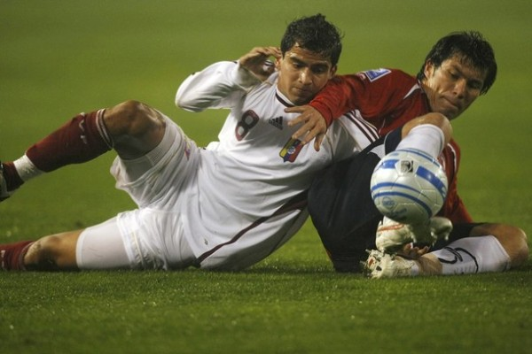 PAREJITOS. Medel disputa el balón en el suelo con Rincón. El 2-2 fue justo por lo visto en el campo (Foto: REUTERS)
