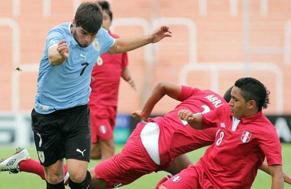 Leonardo Mendoza intenta en vano contener la arremetida del uruguayo Gonzalo Latorre (Foto: losandes.com.ar)