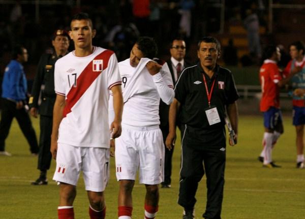 UNA PENA. Arroé y Noronha salen desolados del campo de juego ante la mirada atónita de policías, e integrantes del cuerpo técnico de la selección peruana. (Foto: diario La Voz de Arequipa)