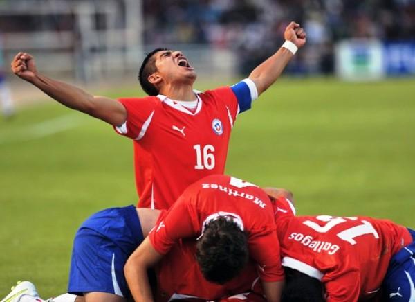 GRITO DE GUERRA. El capitán chileno, Mirco Opazo levanta las manos al cielo en señal de victoria tras el tanto de Lorenzo Reyes. (Foto: AFP)