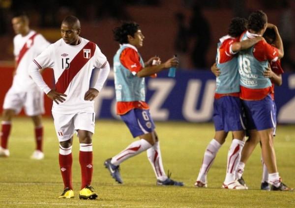 LAS DOS CARAS DEL PARTIDO. Mientras los jugadores chilenos festejan el triunfo de su escuadra, un desconsolado Bazán se retira lentamente de la cancha. (Foto: AFP)