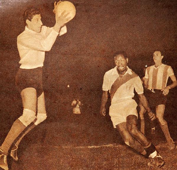 Rogelio Domínguez, arquero de Argentina, atrapa la pelota en una de sus varias intervenciones en el empate contra Perú mientras Guillermo Barbadillo frena su acción durante los Panamericanos de 1956 (Recorte: revista Estadio de Chile)