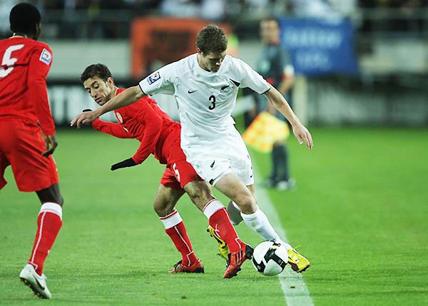 Tony Lochhead supera a Mohammed Hubail en la lucha por el balón. En Wellington, un gol de Rory Fallon marcará la clasificación de los oceánicos a Sudáfrica 2010. (Foto: Scoop NZ)